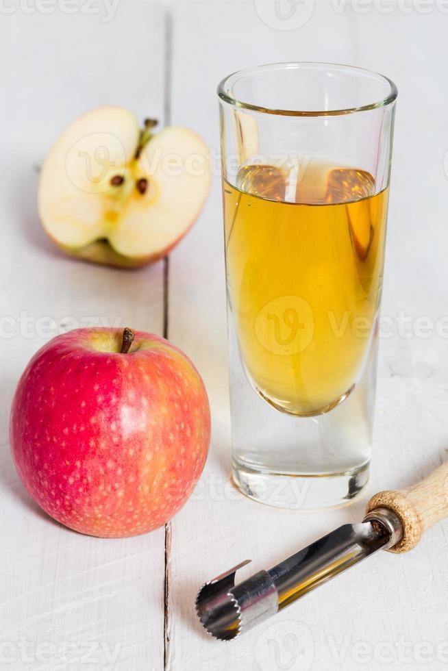 jugo de manzana recién exprimido en vidrio sobre madera foto