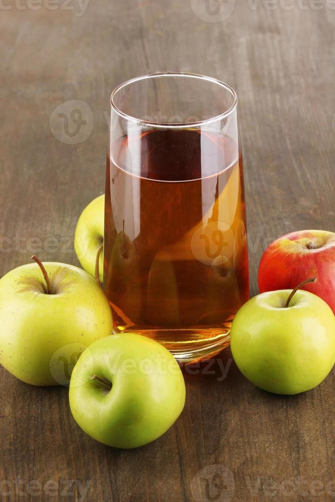 útil jugo de manzana con manzanas alrededor en mesa de madera foto