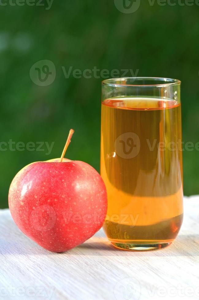 vaso de delicioso jugo de manzana y manzana en la mesa foto