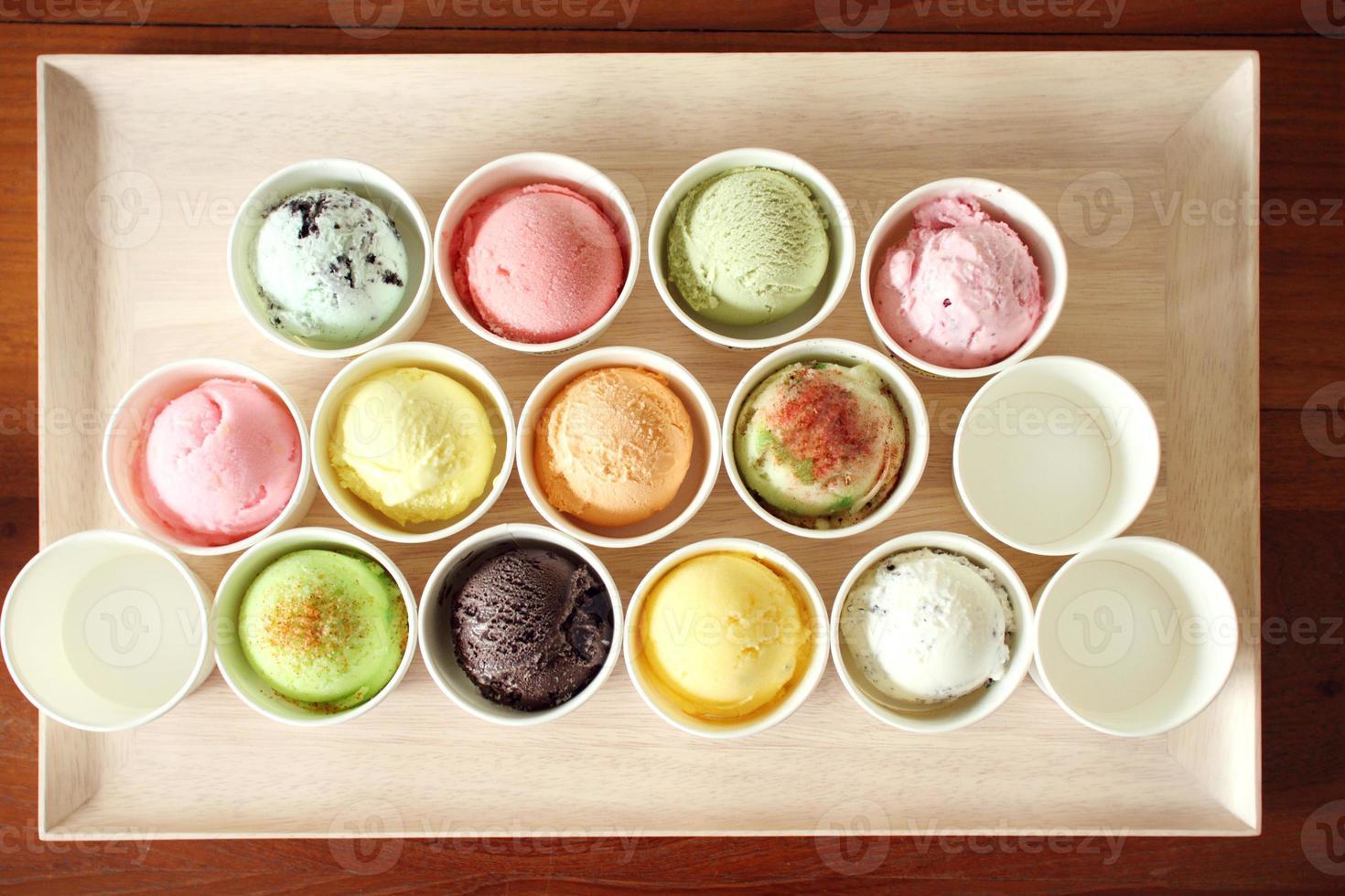 cucharada de helado dulce y colorido en placa de madera foto