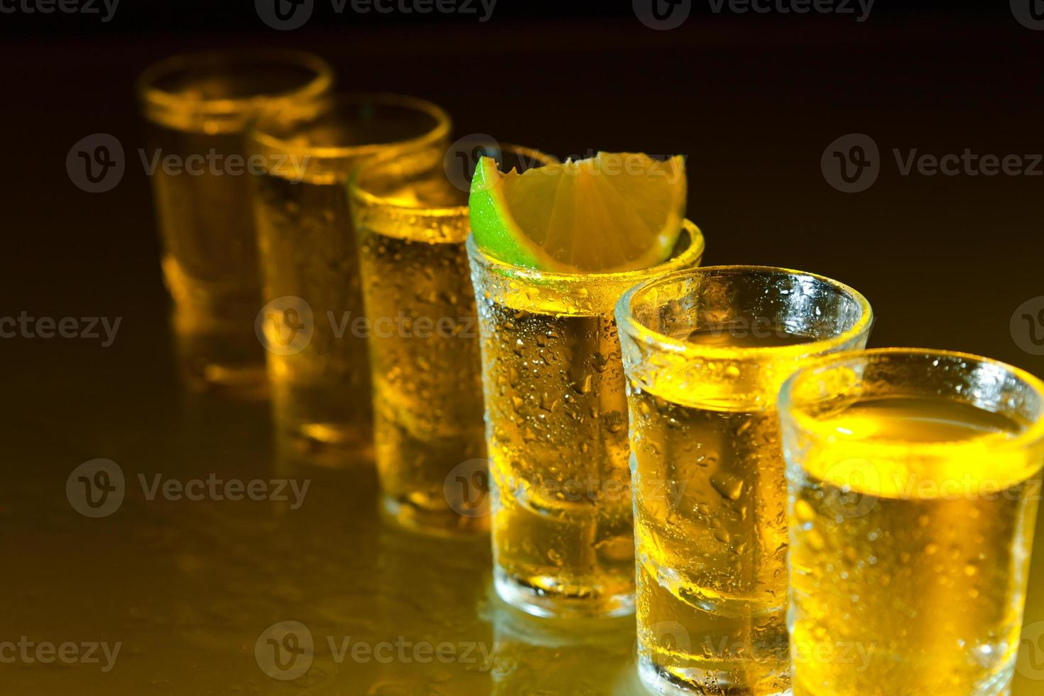 tequila and lime on glass table photo