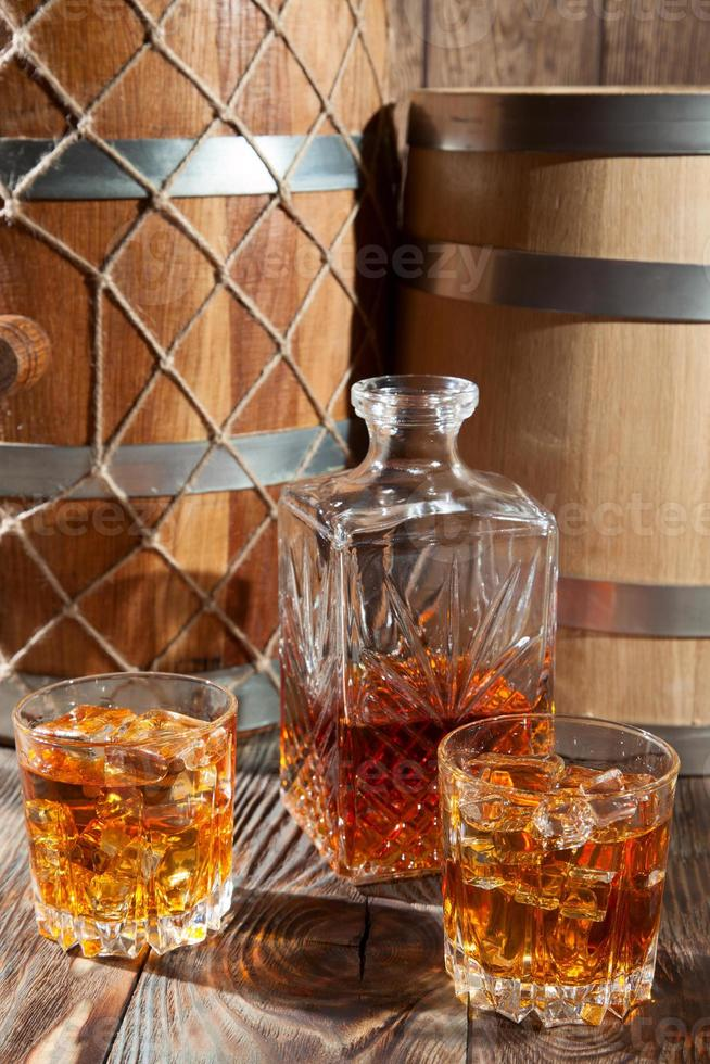 Two glasses of whiskey with ice and decanter photo