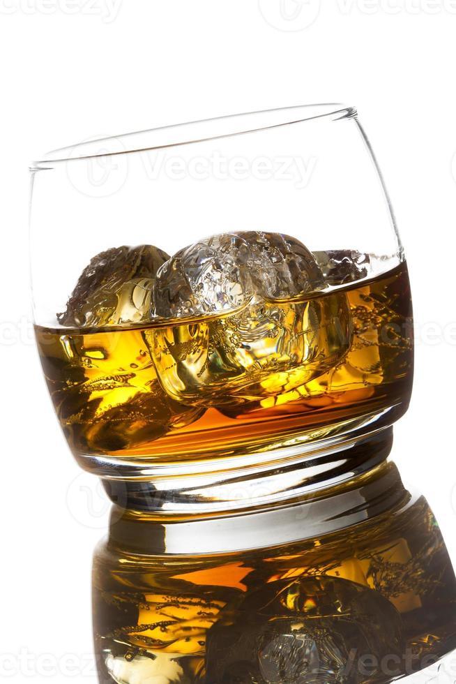 whisky alcohólico bourbon en un vaso con hielo foto