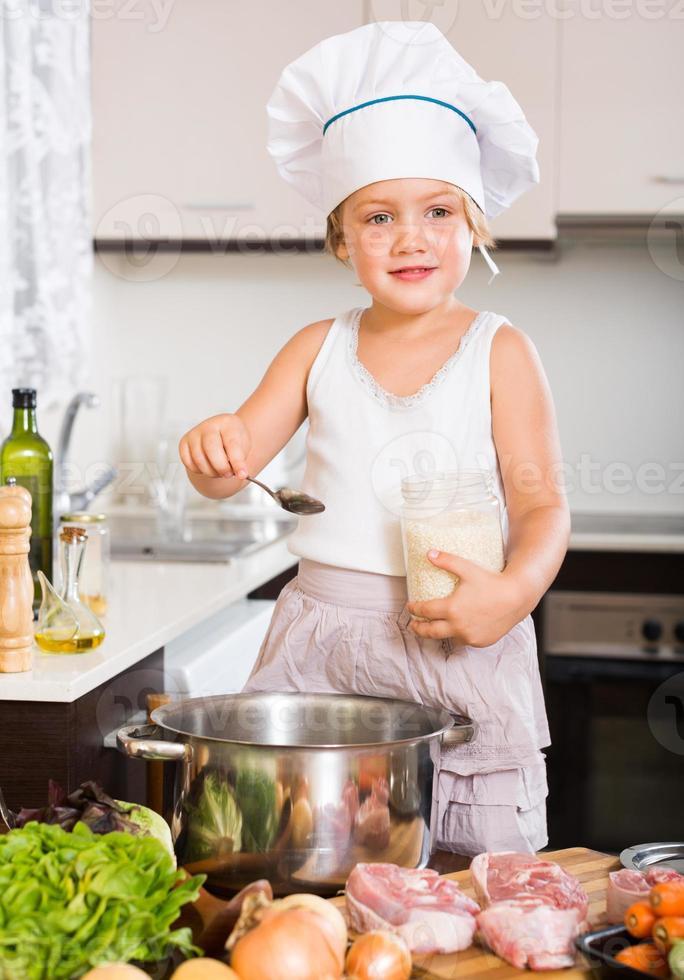 Niña cocinando con carne foto