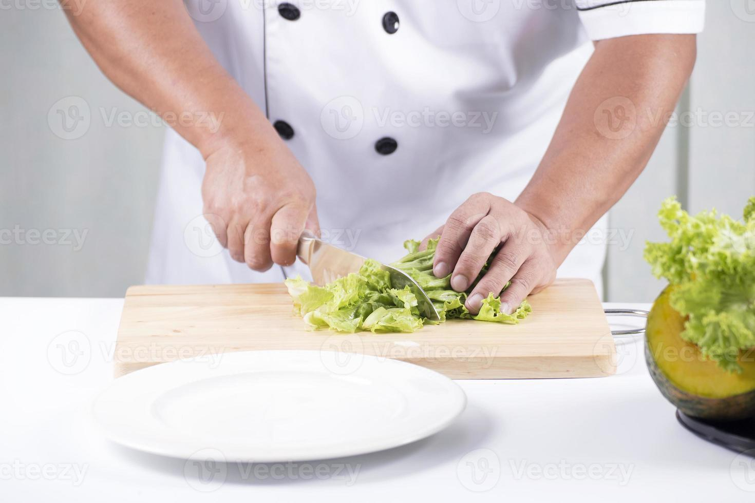 chef cortando lechuga foto