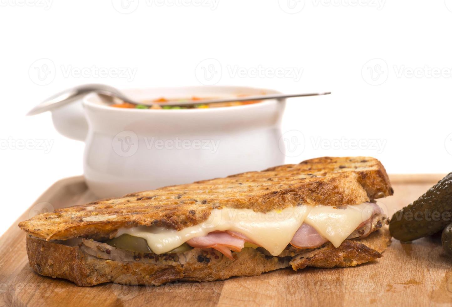 Delicioso panini de jamón, cerdo y queso suizo con sopa de verduras foto