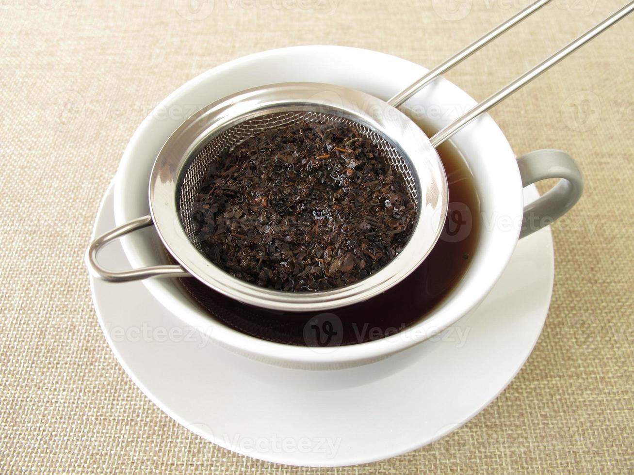 té negro en colador de té foto