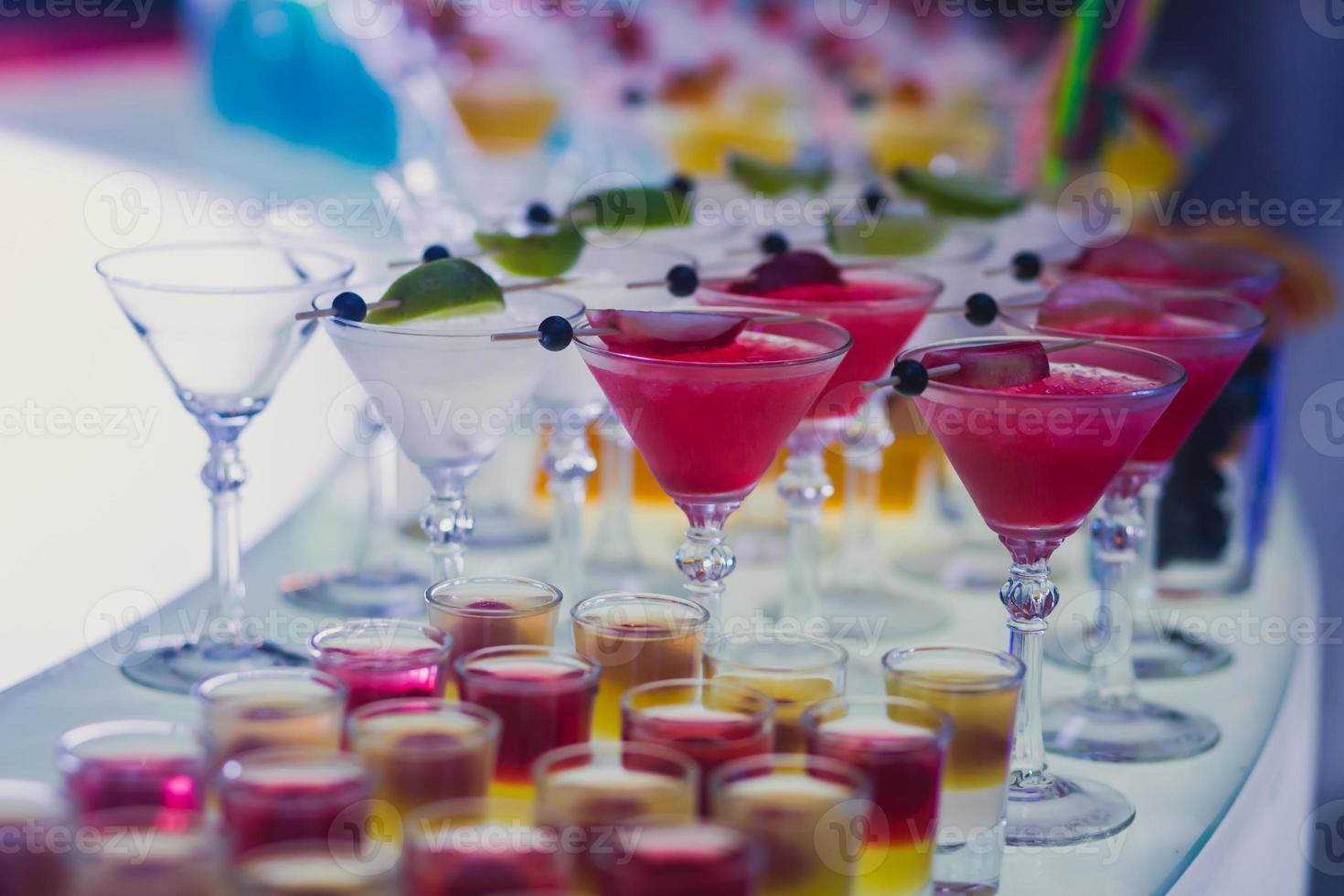 línea de diferentes cócteles de alcohol en una fiesta nocturna al aire libre foto