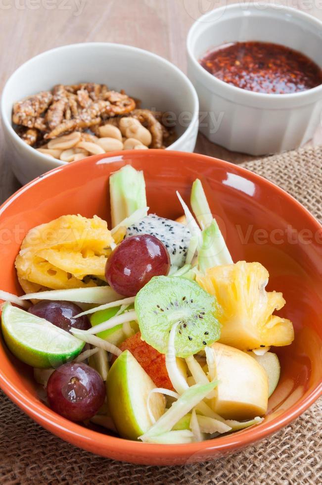 Ensalada de frutas deliciosas en placa en primer plano de la mesa foto