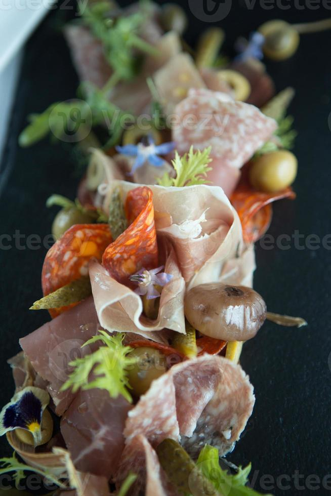 Charcuterie selection including salami, chorzio, parma ham and salad garnish. photo