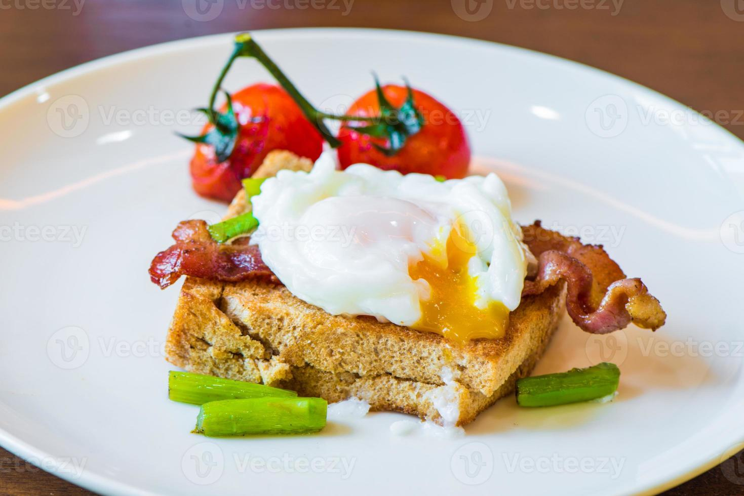 Sandwich with poached egg, parma ham and tomato photo