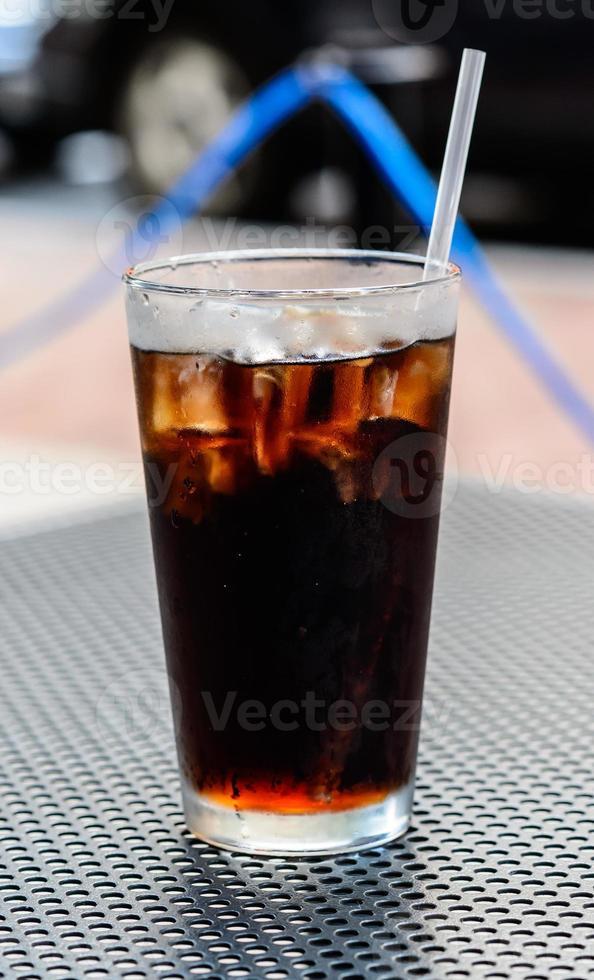 vaso de cola con cubitos de hielo foto