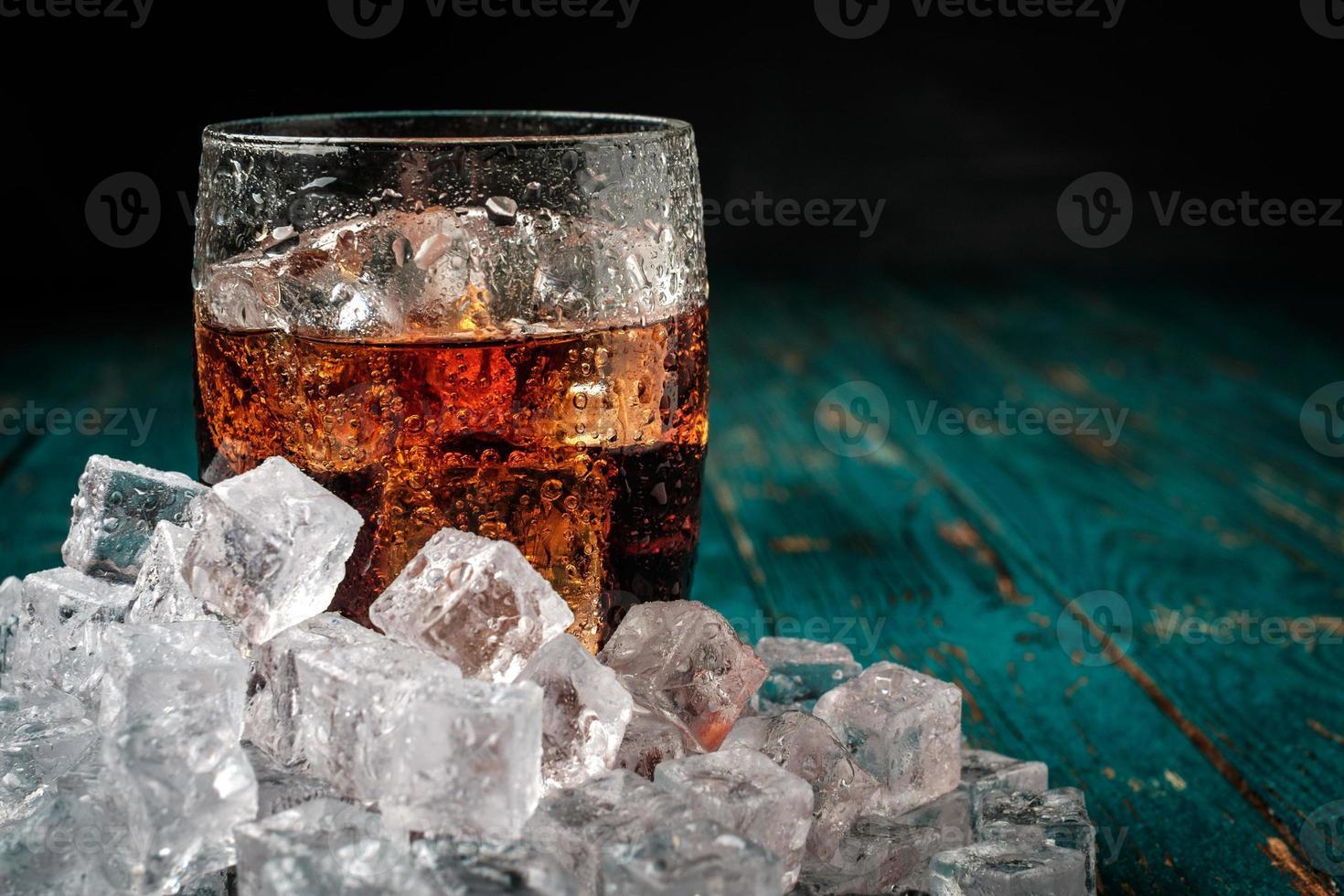 Vaso de cola con hielo en una mesa de madera. foto