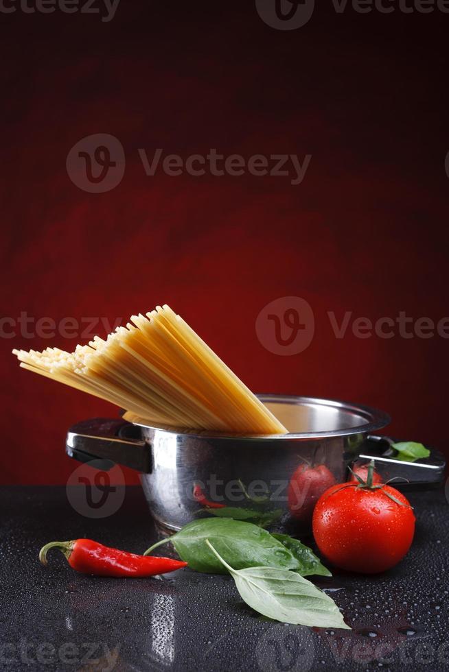 spaghetti in pan with tomato and basilic photo