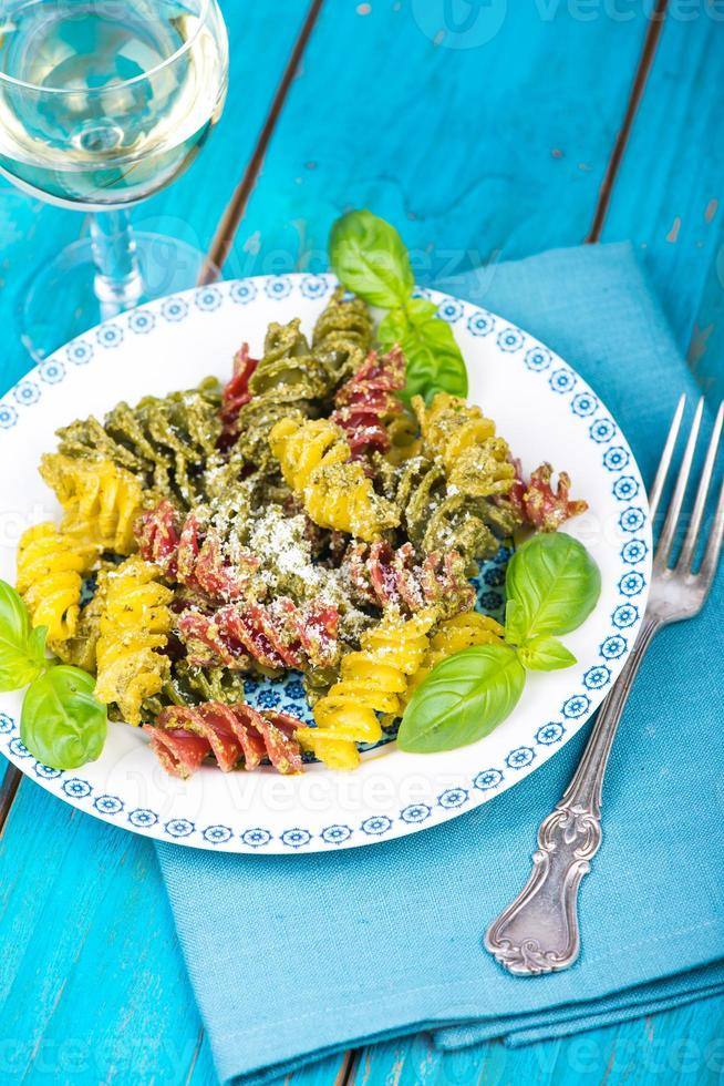 Italian pasta with pesto and parmesan cheese photo