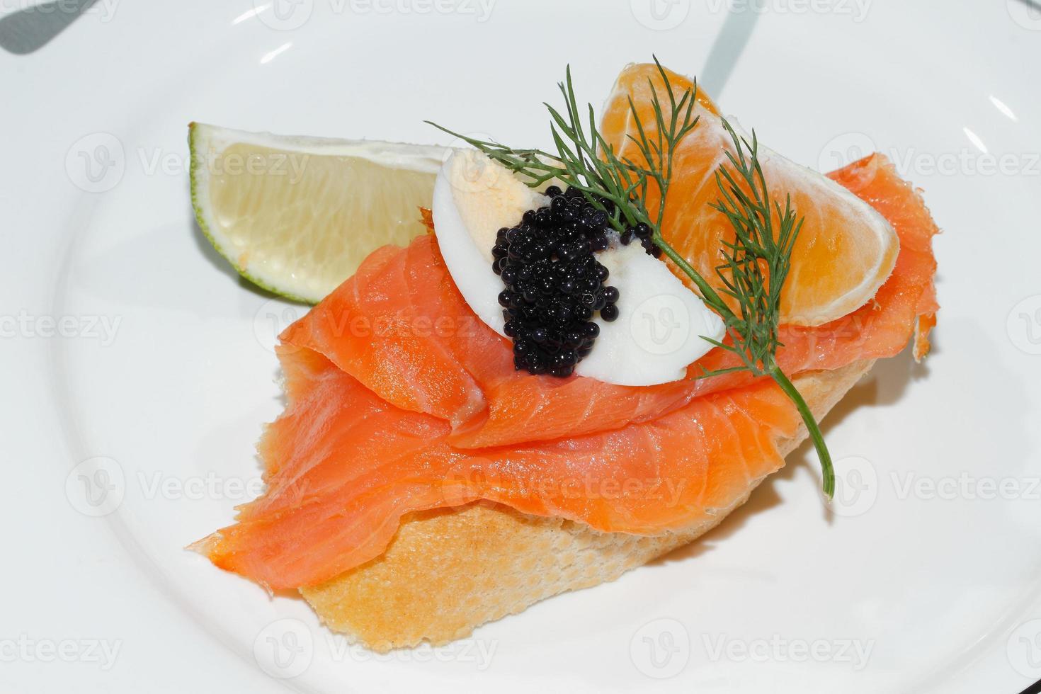 Baguette, smoked salmon, egg, caviar, orange photo