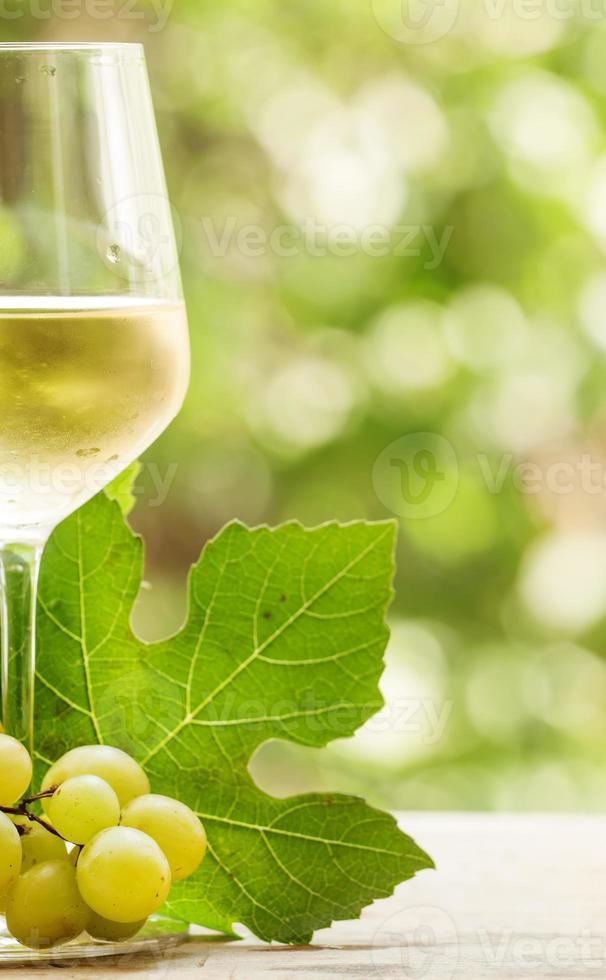vino blanco coid y uvas verdes sobre fondo borroso natural foto