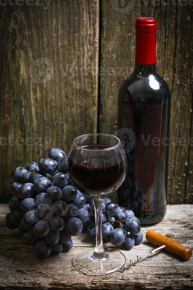 Botella de vino tinto, uva y sacacorchos en mesa de madera foto