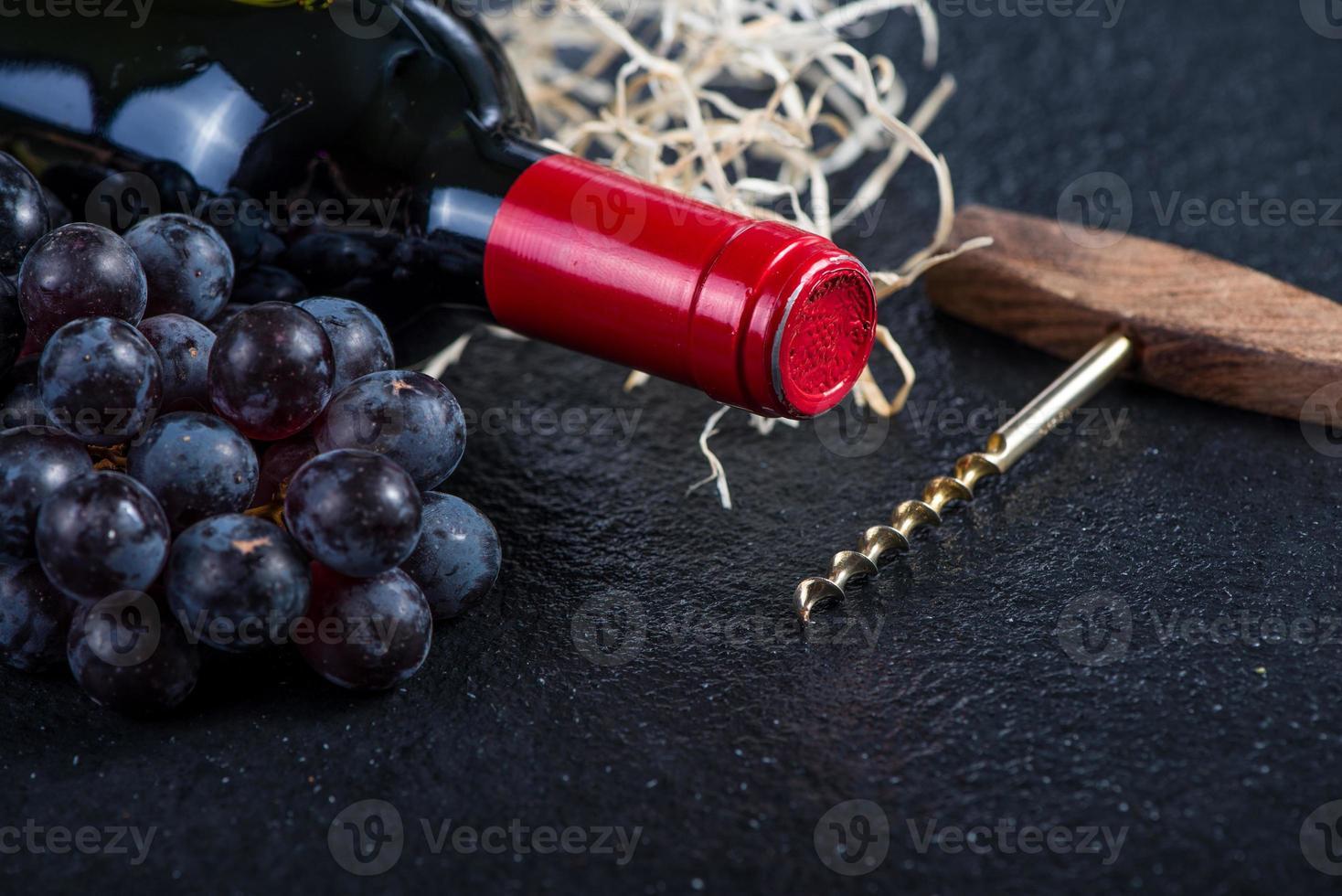 botella de vino tinto con uvas y sacacorchos foto