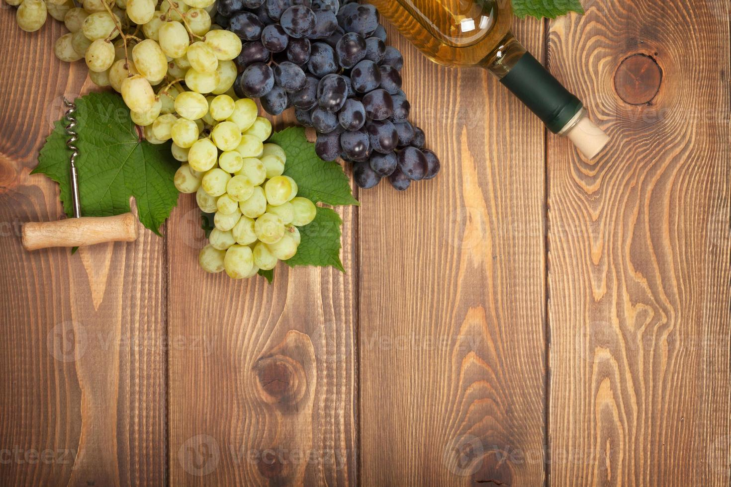 White wine bottle and bunch of grapes photo