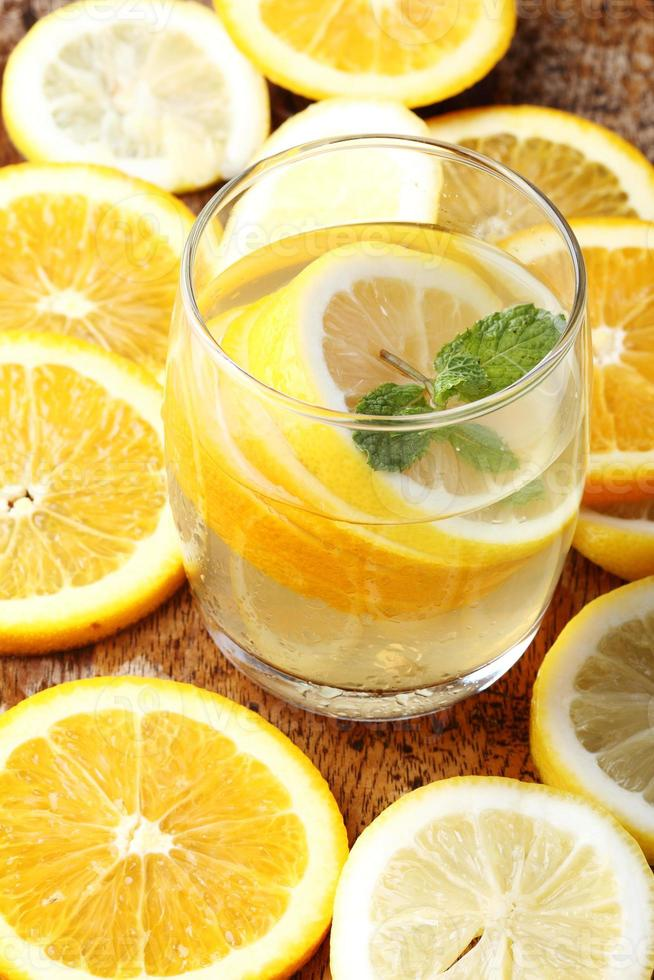 drink and stack of citrus fruits slices. Oranges and lemons. photo