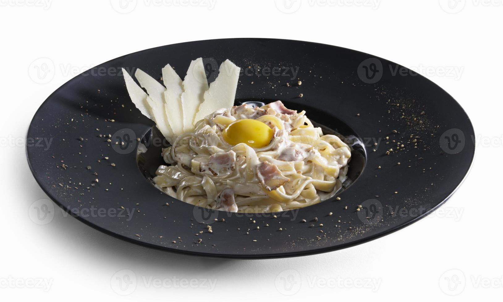 Pasta carbonara decorated with slices of parmesan and yolk isolated photo