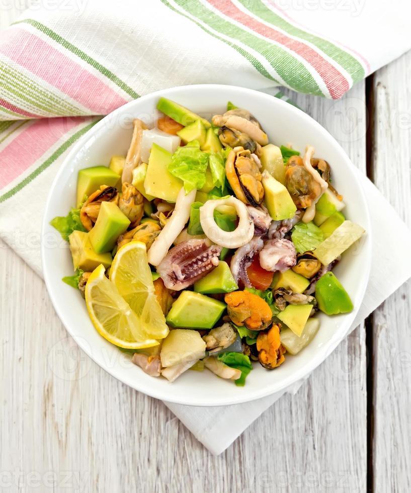 Salad seafood and avocado on white board photo