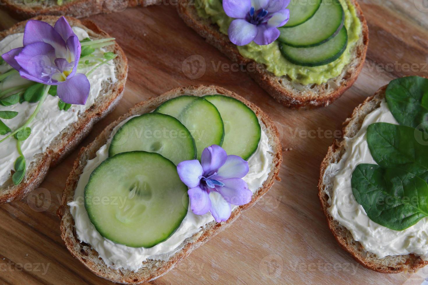 Green sourdough open face sandwiches with purple edible flowers photo