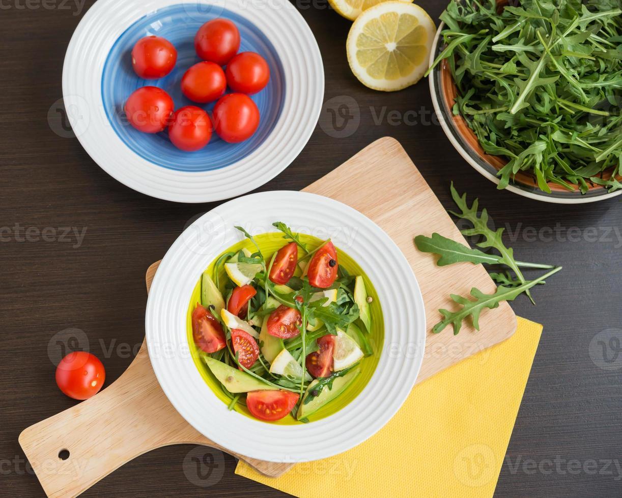 Healthy food. Fresh salad of arugula, cherry tomatoes, avocado photo
