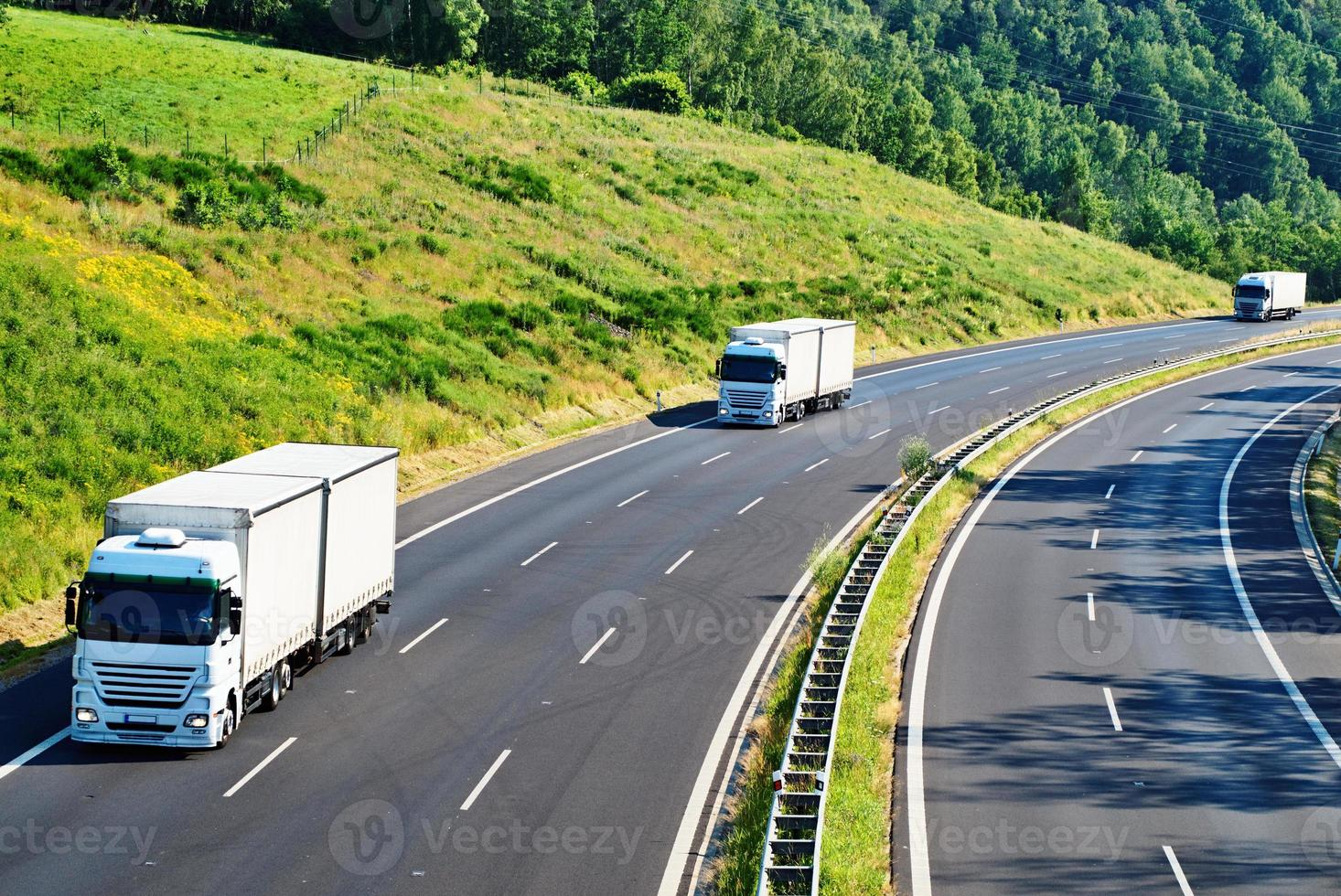Highway with three oncoming white truck in a wooded landscape photo
