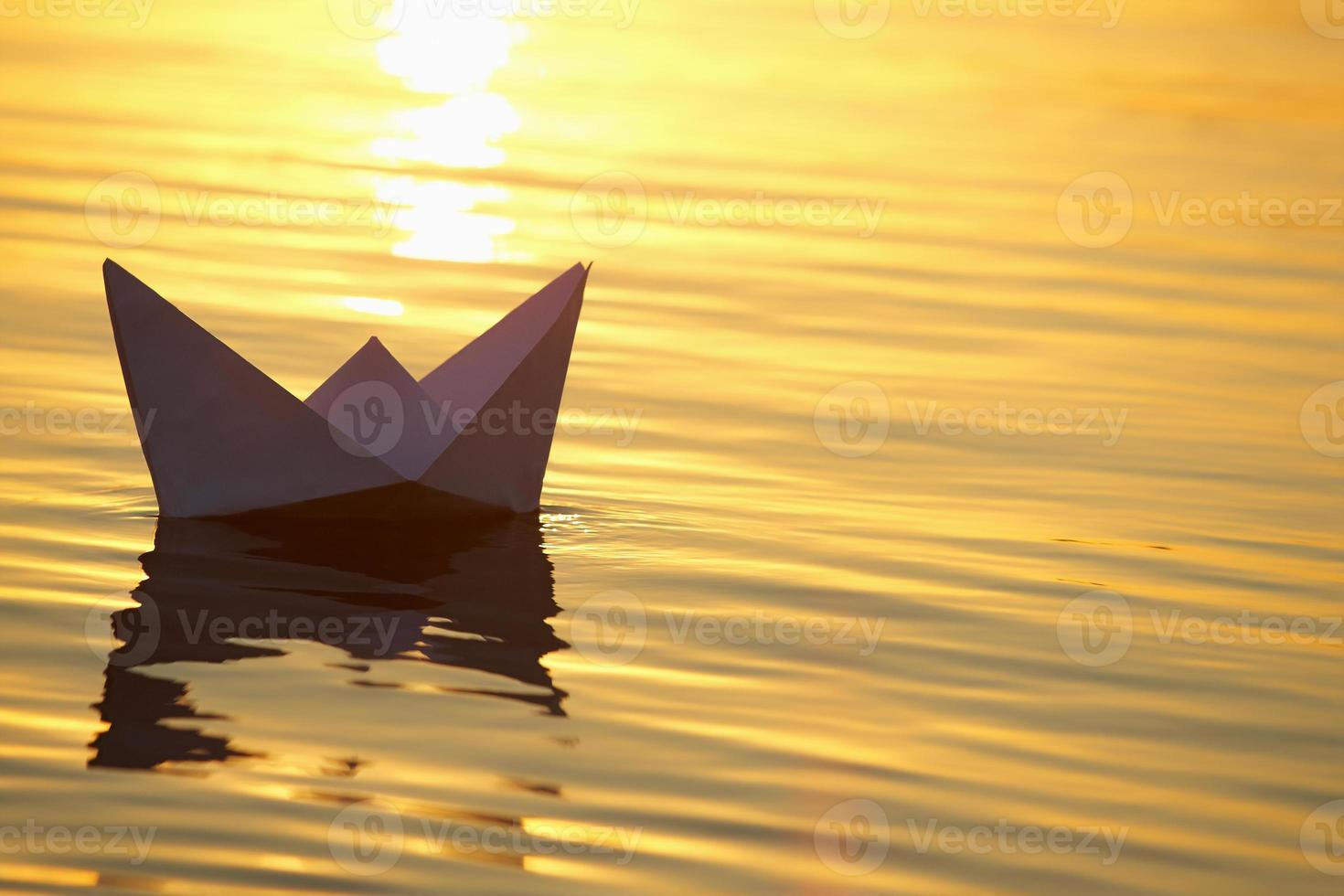 Paper boat sailing on water with waves photo