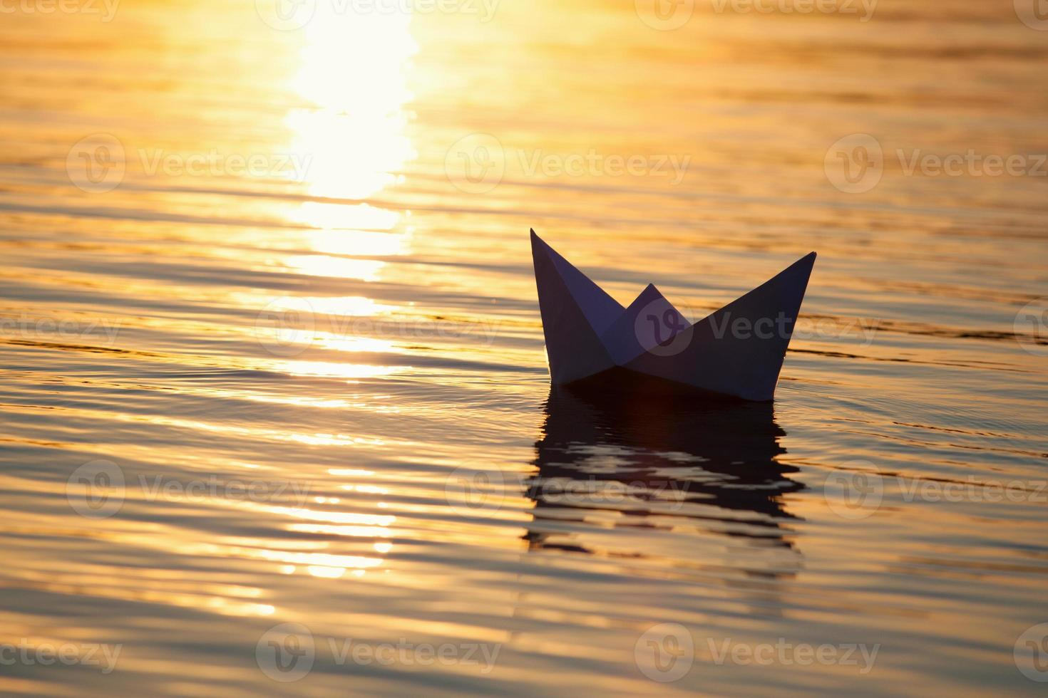 Paper boat sailing on water with waves  and ripples photo