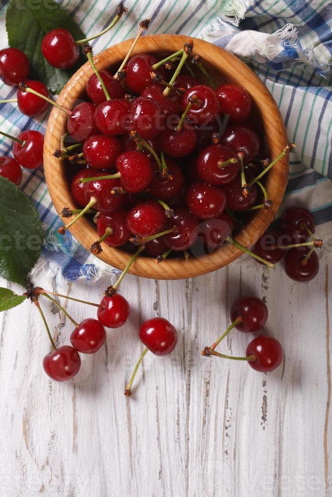 Red cherries in a wooden bowl vertical view above, rustic photo