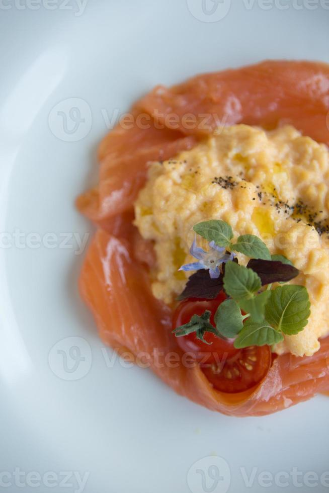 Smoked salmon, scrambled eggs and a cherry tomato garnish. photo
