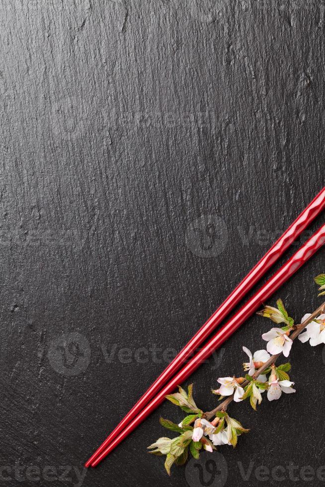 palillos de sushi japonés y flor de sakura foto
