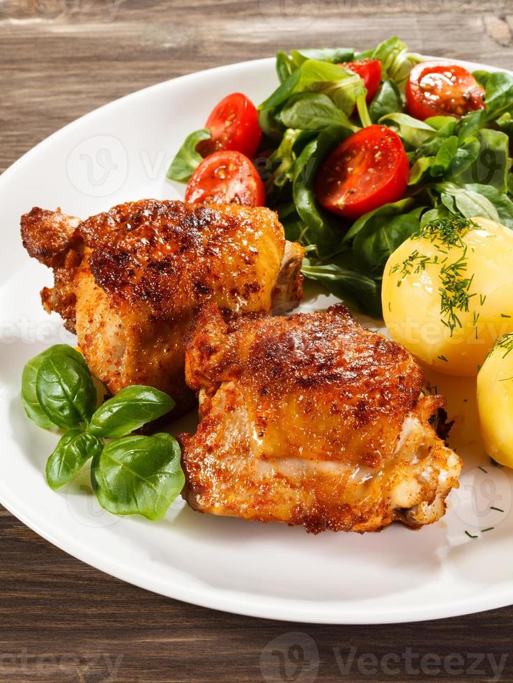 Roasted chicken legs, boiled potatoes and vegetables photo