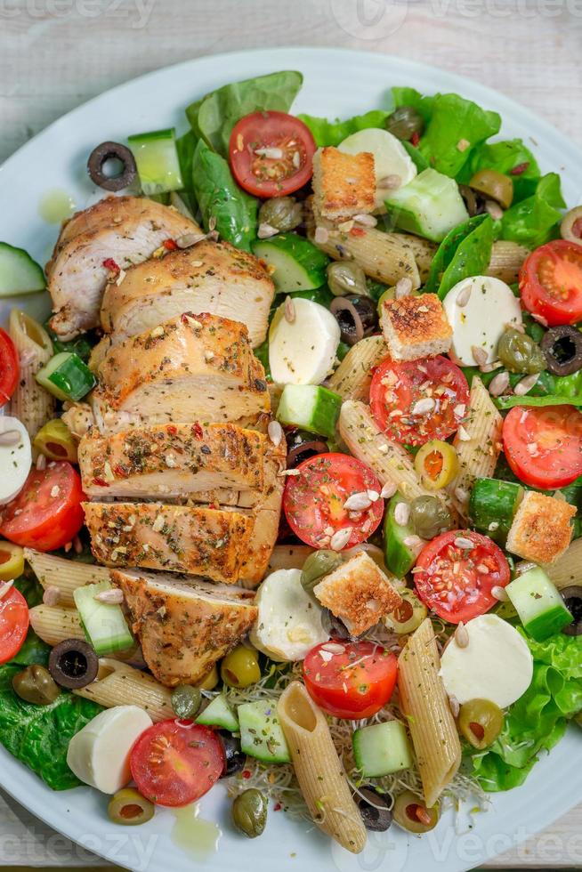 Caesar salad with fresh vegetables and chicken photo