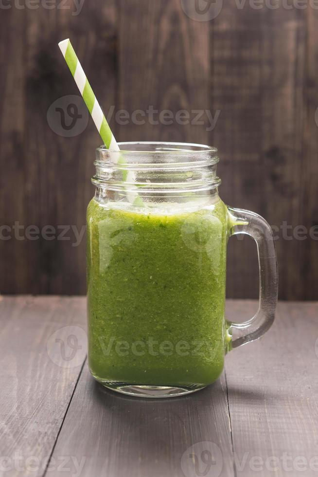 vegetales verdes saludables y batido de frutas verdes en madera rústica foto