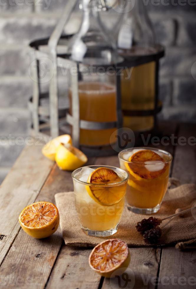 Lemonade in glasses and bottles made of grilled lemons. Cider. photo