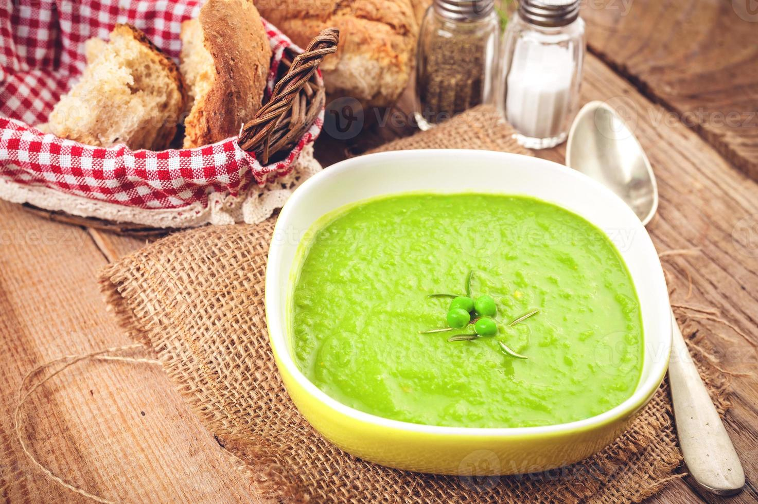 Green pea soup in bowl with bread and sour cream photo
