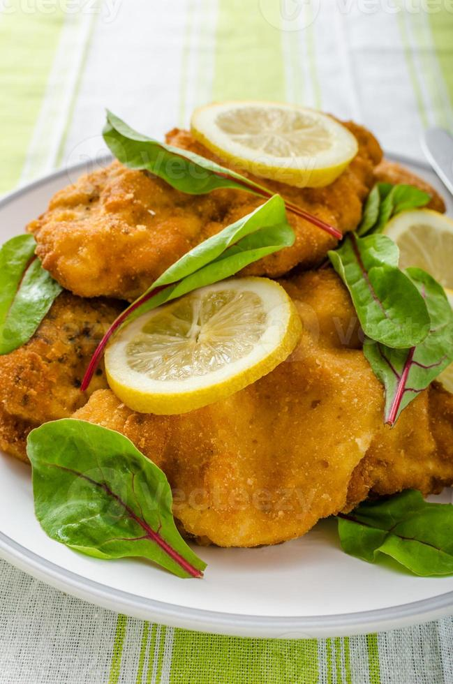 Fried schnitzel with herbs and lemon photo