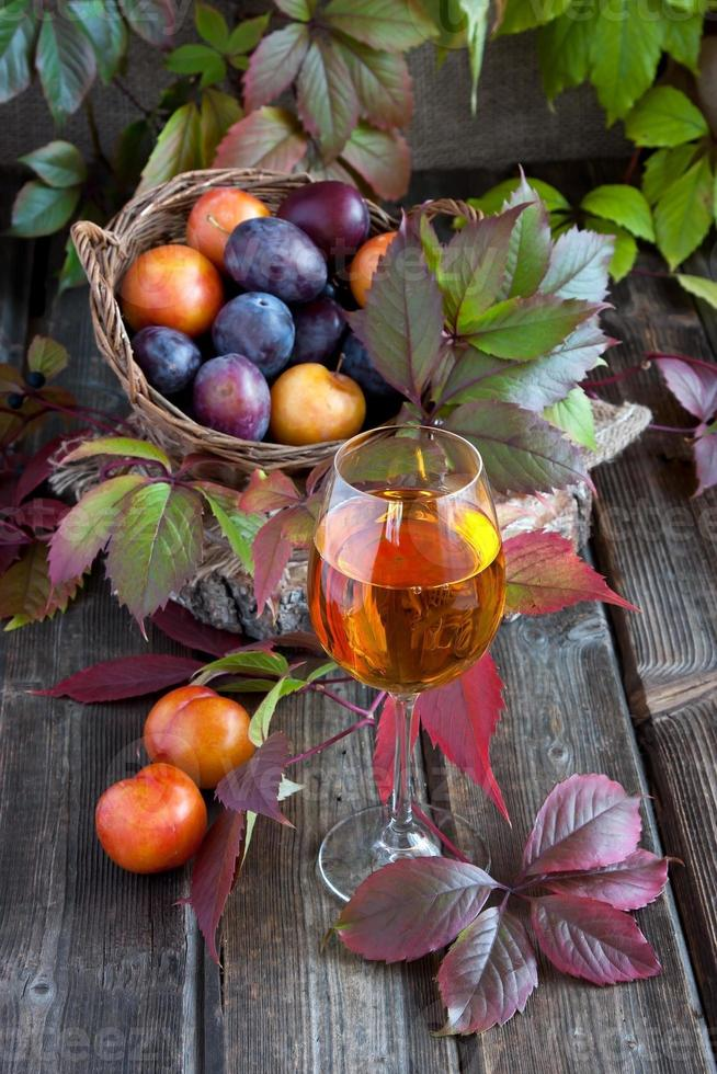 Tasty plums and glass of the  wine photo