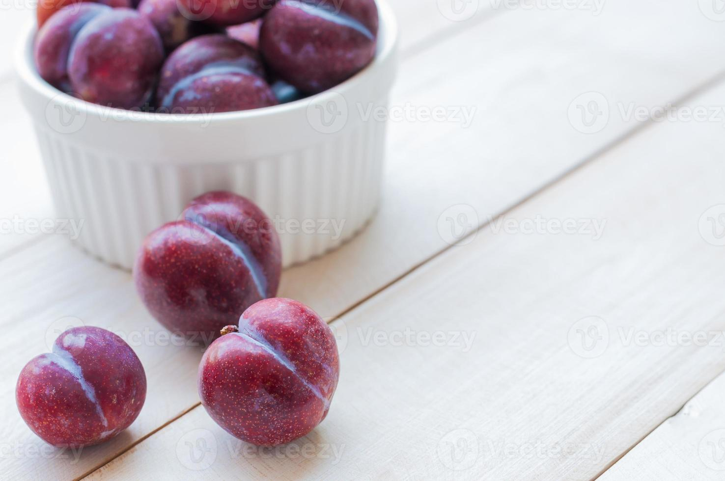 Sweet plums on wooden background photo