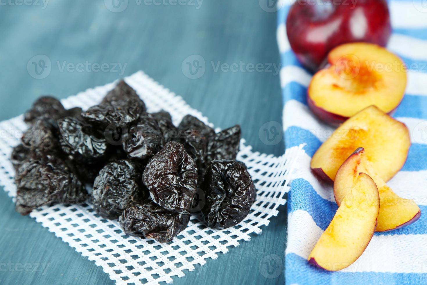 Fresh and dried plums  on napkin, on wooden background photo