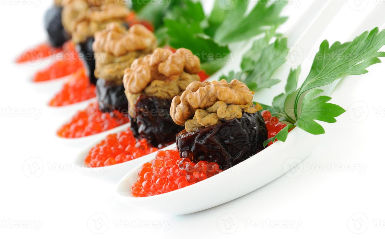 Prunes stuffed with liver pate  nuts in a red caviar photo