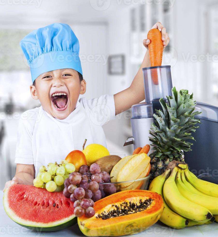 pequeño chef está haciendo jugo de frutas foto