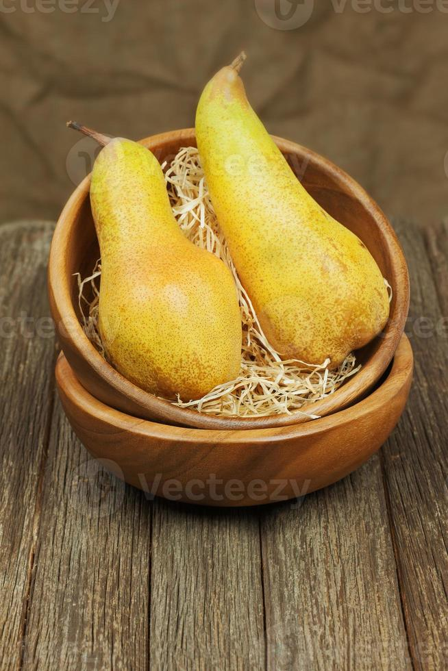 Ripe pears in bowl on wooden background. photo