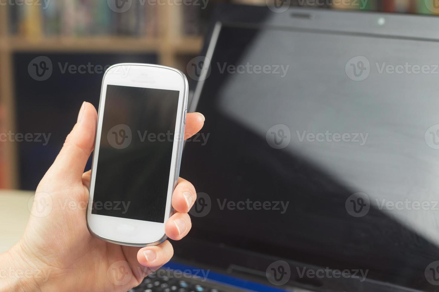 sosteniendo un teléfono celular foto