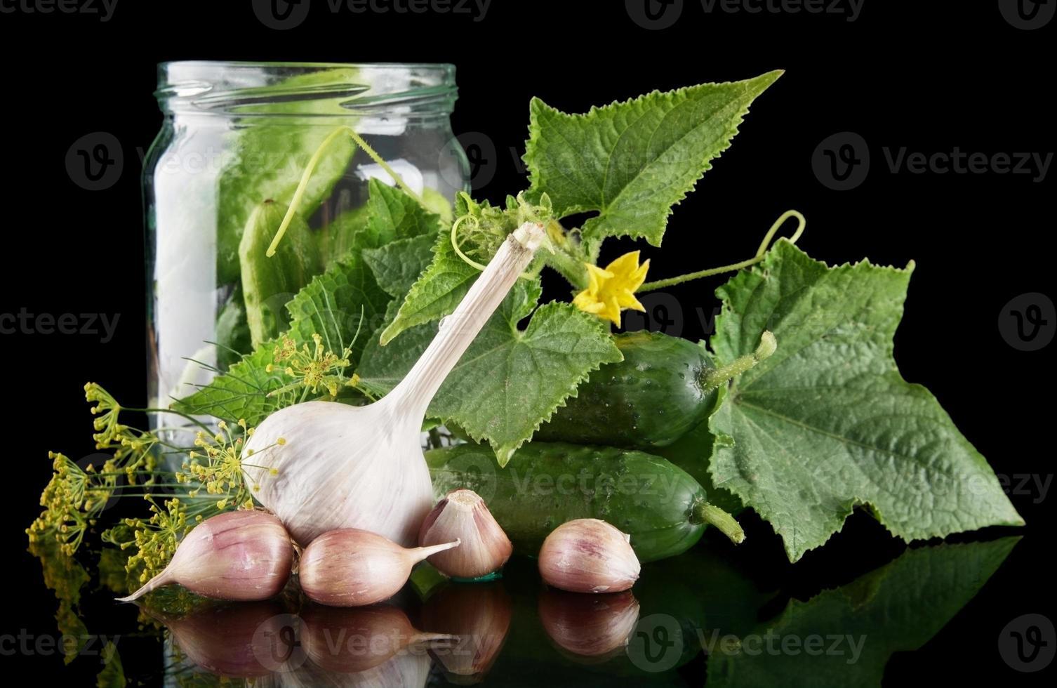 Cucumbers in jar preparate for pickling on black photo