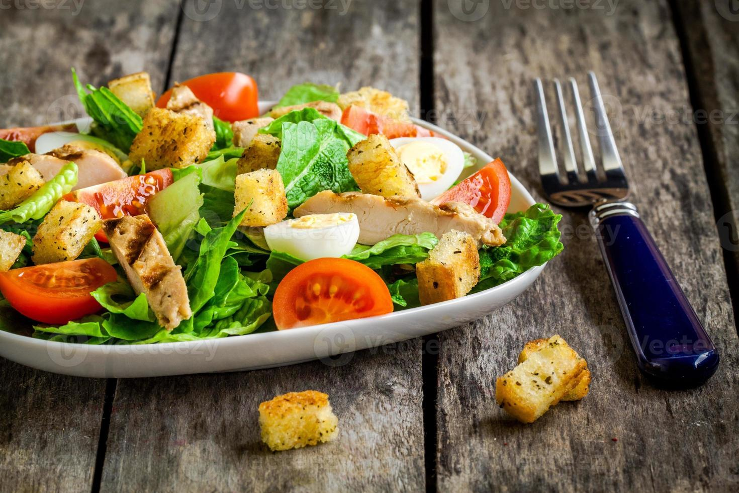 Caesar salad with croutons, quail eggs, tomatoes and grilled chicken photo
